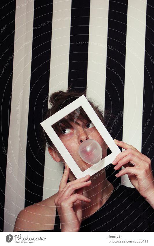 Frau mit Kaugummiblase und Rahmen vor schwarz weiß gestreiftem Hintergrund schwarz weis gestreift Porträt Farbfoto Gesicht lustig feminin Studioaufnahme Blase