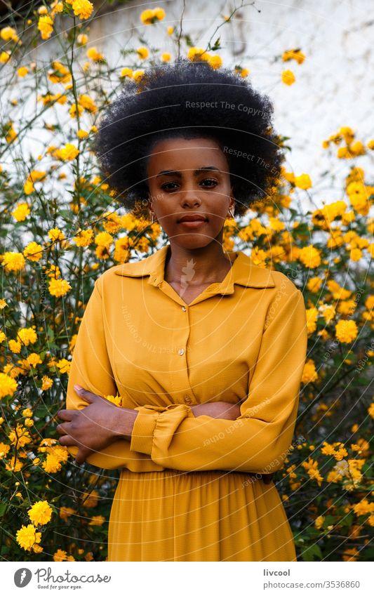 junge afroamerikanische Frau in gelbem Kleid, die sich an einem Garten mit gelben Blumen erfreut schwarze Frau Mädchen Menschen genießend Porträt Lifestyle cool