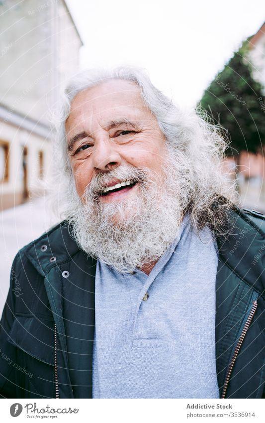 Fröhlicher alter Mann mit grauen Haaren und langem Bart schaut in die Kamera heiter Vollbart Glück Senior Reisender Weisheit Straße Porträt Großstadt Rentnerin