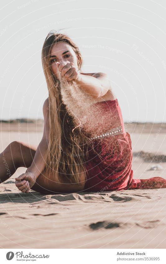 Stilvolle junge Dame sitzt am Strand und schüttet Sand durch die Finger Frau träumen eingießen sinnlich Sommer allein Küste Freiheit charmant blond attraktiv