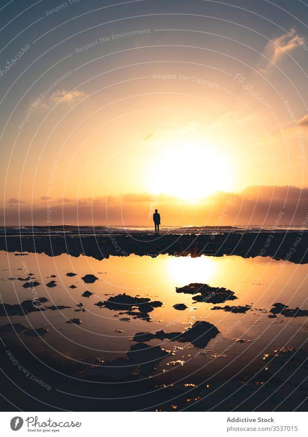 Nicht erkennbare Person, die bei Sonnenuntergang am Wasser steht Ufer Himmel Abend Silhouette hell Fuerteventura Spanien Kanarische Inseln Windstille Dämmerung