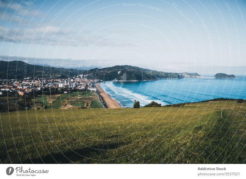 Malerische Aussicht vom grünen Hügel auf die Küste und die Stadt an einem sonnigen Tag in Spanien Tal Meeresufer Landschaft Natur Himmel malerisch friedlich