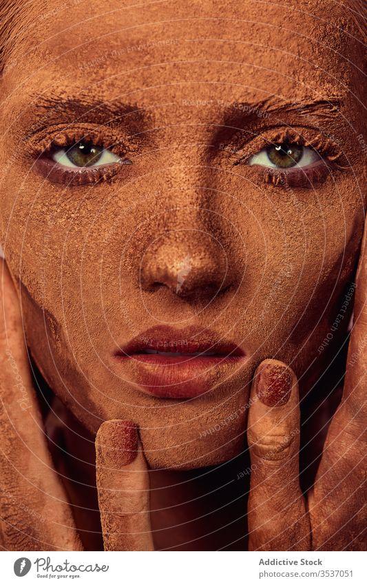 Weibliches Modell mit Schokolade im Gesicht Frau Pulver Gesicht berühren Konzept Deckung Leckerbissen sinnlich Vorschein jung schön Menschliches Gesicht