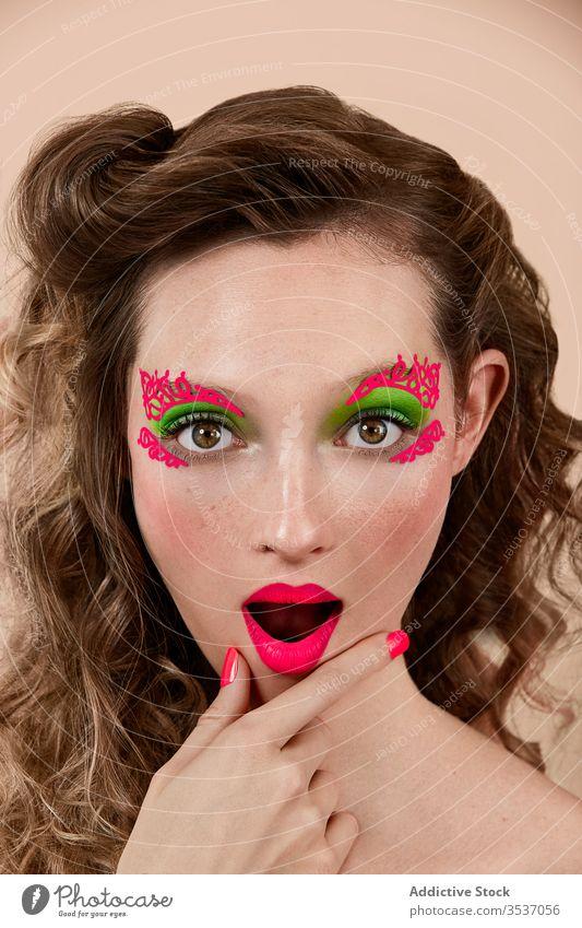 Erstaunte Frau mit leuchtendem Make-up farbenfroh erstaunt Konzept Stil Kinn reiben Mund geöffnet Model jung Vorschein Erstaunen Überraschung hell lebhaft