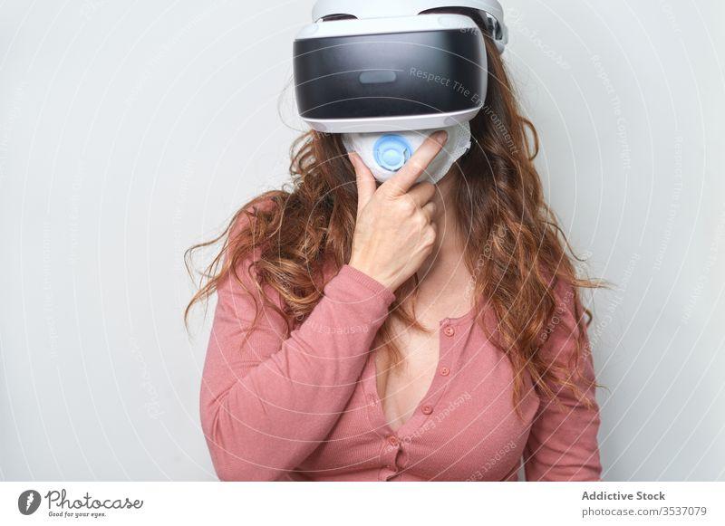 Nicht erkennbare Frau mit Headset und Atemschutzmaske während COVID 19 Mundschutz VR Innovation Technik & Technologie unterhalten Quarantäne Bund 19 behüten