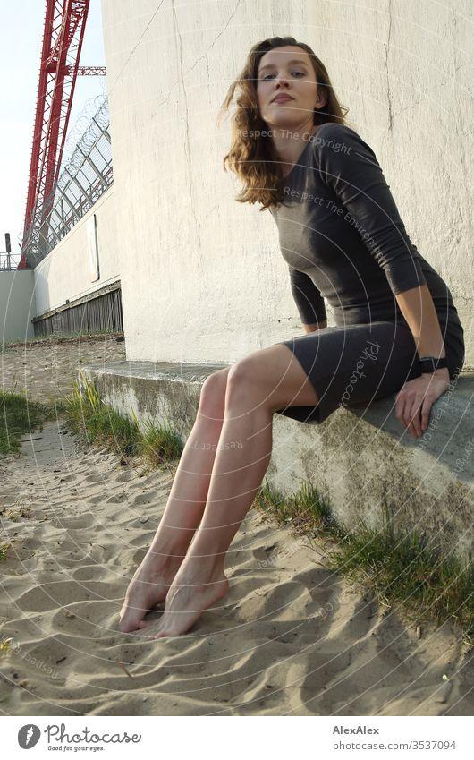 Porträt einer jungen Frau vor einer Betonmauer am Strand Mädchen bereits schlank brünett Locken lange Haare Abend Schönheit und Schönheit 18-25 Jahre