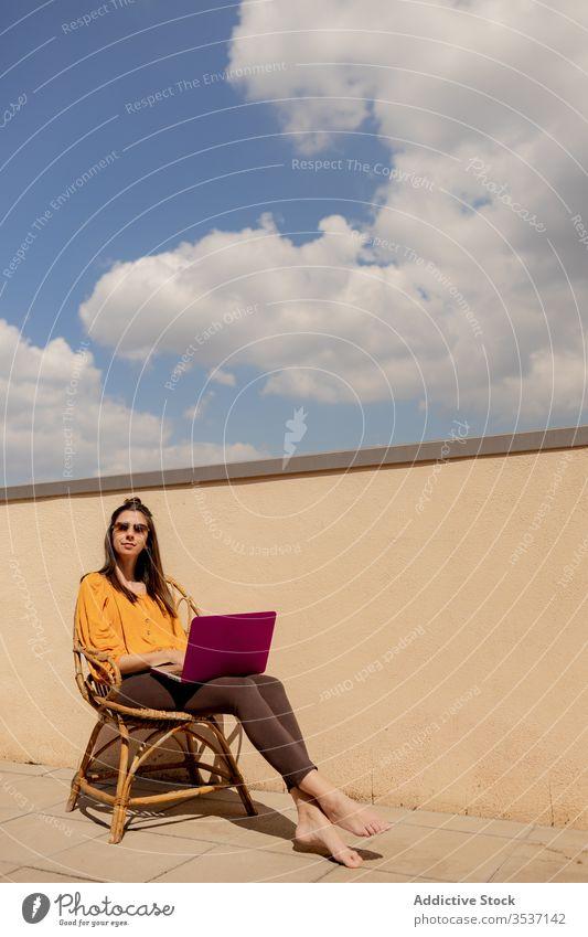 Junge Frau mit Laptop auf Stuhl sitzend Terrasse heimwärts Arbeit benutzend genießen freiberuflich Quarantäne Lifestyle Sonnenschein Browsen brünett lässig