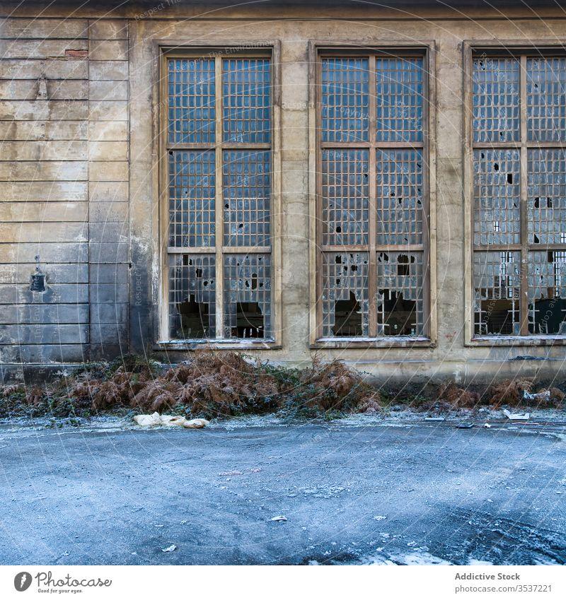 Altes Industriegebäude mit zerbrochenen Fenstern Gebäude Verlassen Wand industriell gebrochen schäbig verwittert Ruine Stein Raster Glas niemand