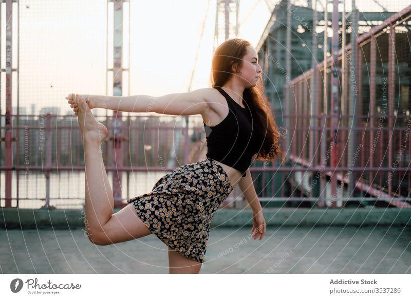 Ruhige Frau beim Yoga auf der Brücke üben Stadtbild beweglich Asana Herr des Tanzes Pose ruhig Großstadt urban Landschaft lässig Outfit Rock Übung Natarajasana