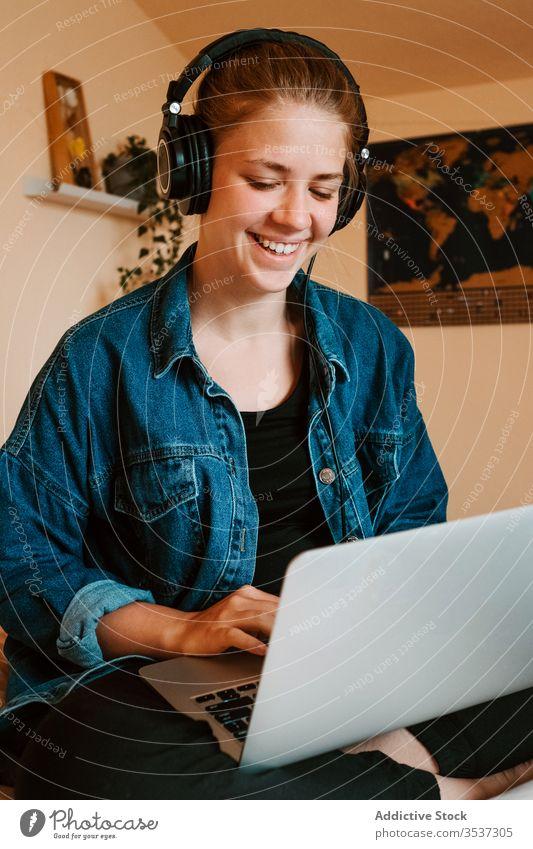Fröhliche junge Frau mit Laptop im hellen Schlafzimmer zu Hause Kopfhörer heimwärts benutzend Bett lesen Surfen soziale Netzwerke zuschauen sich[Akk] entspannen