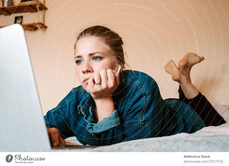 Frau schaut Film auf Laptop im gemütlichen Schlafzimmer heimwärts benutzend Bett liegend zuschauen Surfen soziale Netzwerke zuhören Interesse Filmmaterial