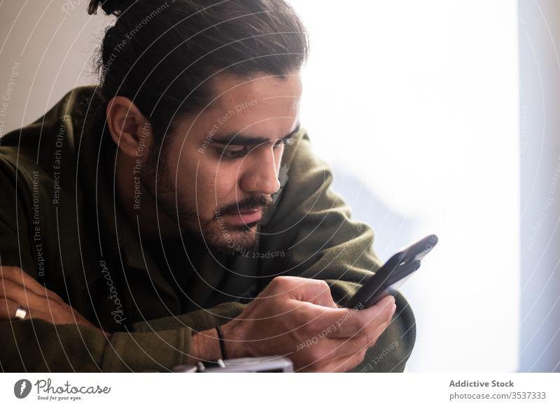 Schwerer Mann benutzt Smartphone in hellem Raum Vollbart benutzend Browsen Surfen besinnlich gutaussehend Licht Nachricht ethnisch Mobile Apparatur