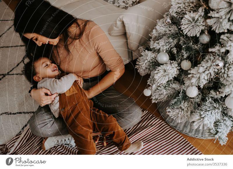Fröhliche, liebevolle Mutter umarmt kleinen Sohn, der auf dem Boden neben dem Weihnachtsbaum sitzt kuscheln Weihnachten heimwärts spielerisch gemütlich Feiertag