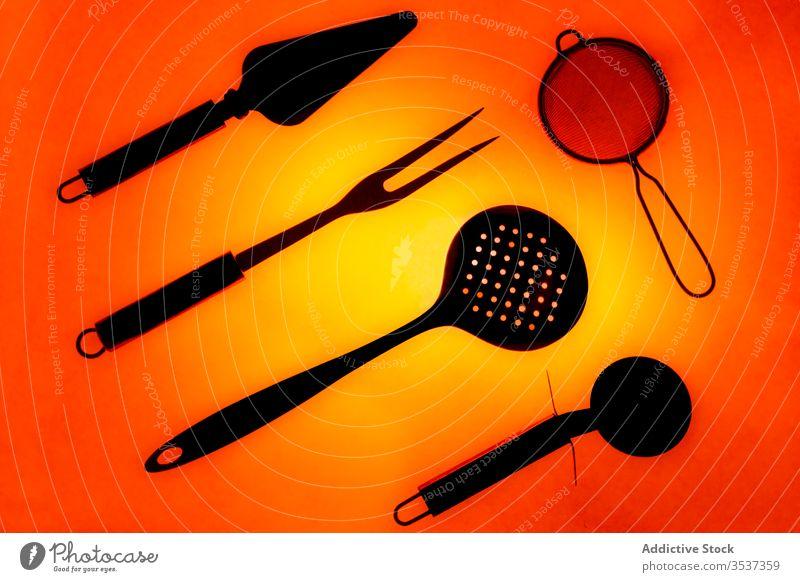 Set mit verschiedenen Küchenutensilien auf blauem Hintergrund Utensil Kulisse Zusammensetzung Ordnung Werkzeug Objekt Gerät schwarz leuchten glänzend Sieb
