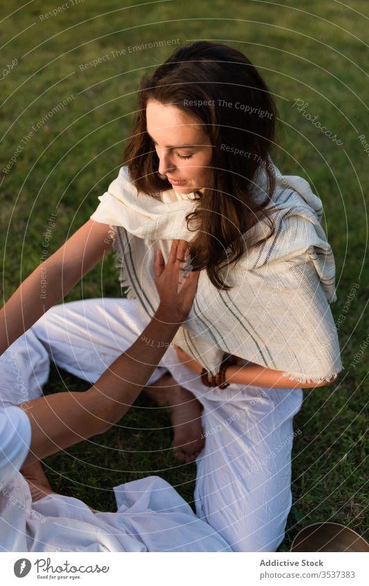 Liebespaar macht Partner-Yoga in der Natur Paar gegenüber meditieren Lotus-Pose Windstille Zen Herz Rasen Lotos Augen geschlossen Magen genießen grün