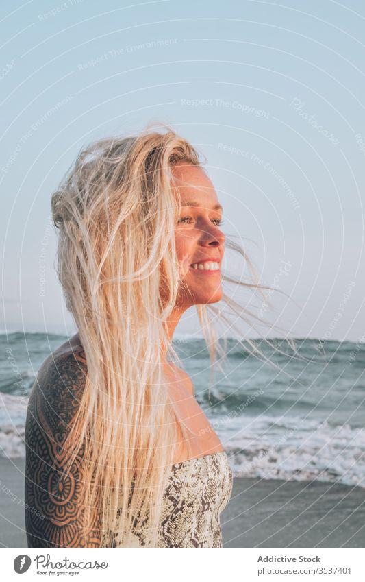 Lächelnde junge Blondine ruht sich bei Sonnenschein am Meeresufer aus Frau Strand Schulter Tattoo blond Sommer Sand Urlaub sich[Akk] entspannen Küste Natur Ufer