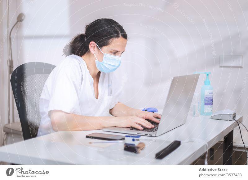 Junge Ärztin mit medizinischer Maske arbeitet am Laptop in der Klinik Frau Arzt Uniform Mundschutz Handschuh Schreibtisch ernst Krankenhaus professionell