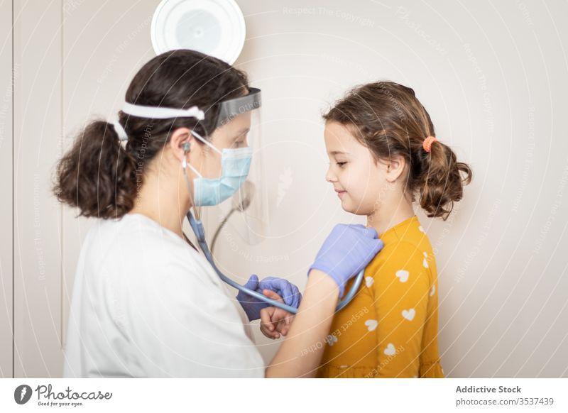 Ärztin untersucht Lungen eines kleinen Mädchens in der Klinik Frau Arzt Mundschutz geduldig Ausfallschritt Stethoskop Krankenhaus Handschuh Lungenentzündung