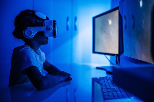 Unbekannter Junge im VR-Headset vor dem Computer sitzend Desktop Monitor Entertainment Video benutzend Gerät Apparatur Brille Drahtlos zuschauen Bildschirm