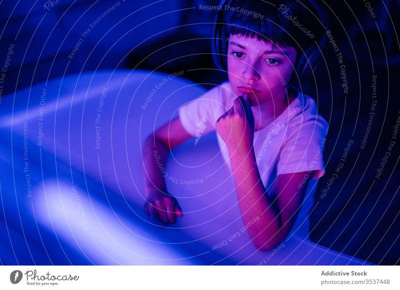 Nachdenklicher Junge mit Kopfhörern am Tisch sitzend nachdenklich Melancholie Kinn berühren zuhören Musik Denken nachdenken benutzend Apparatur Gerät Headset