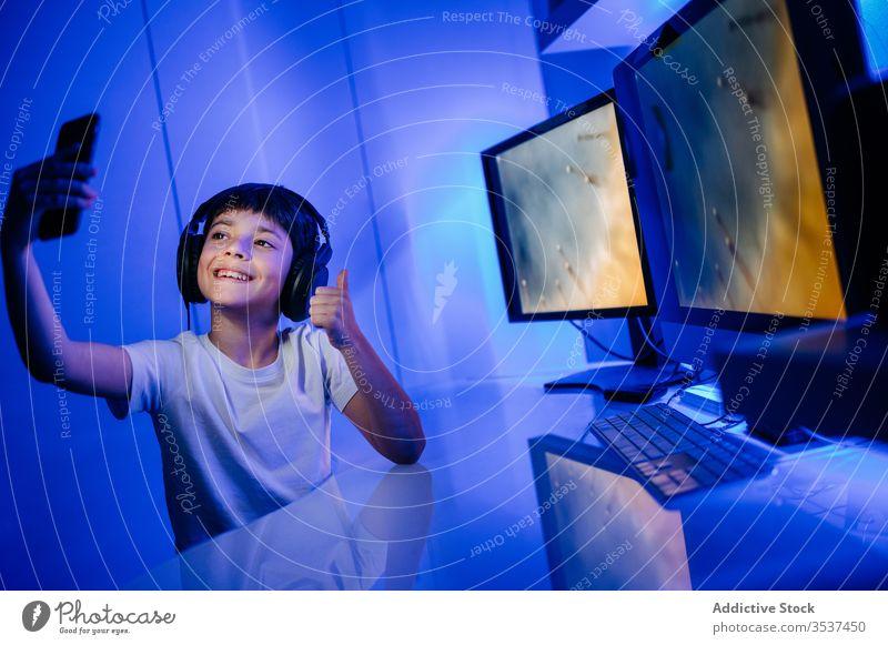 Fröhlicher Junge mit Headset, der sich zu Hause am Smartphone selbstständig macht Selfie Kopfhörer Daumen hoch Zahnfarbenes Lächeln Desktop Computer heimwärts