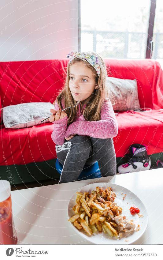 Mädchen isst zu Hause zu Mittag heimwärts essen Mahlzeit Abendessen Wohnzimmer Mittagessen Lebensmittel Sofa sitzen ruhen lässig geschmackvoll Speise Kind