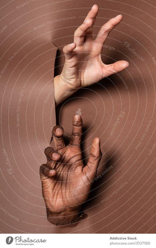 Anonymes gemischtrassiges Ehepaar durch Papiervorhang geplatzt Paar Hand Golfloch Gardine zeigen Zusammensein Finger Freude Freizeit Spaß Arme Handfläche