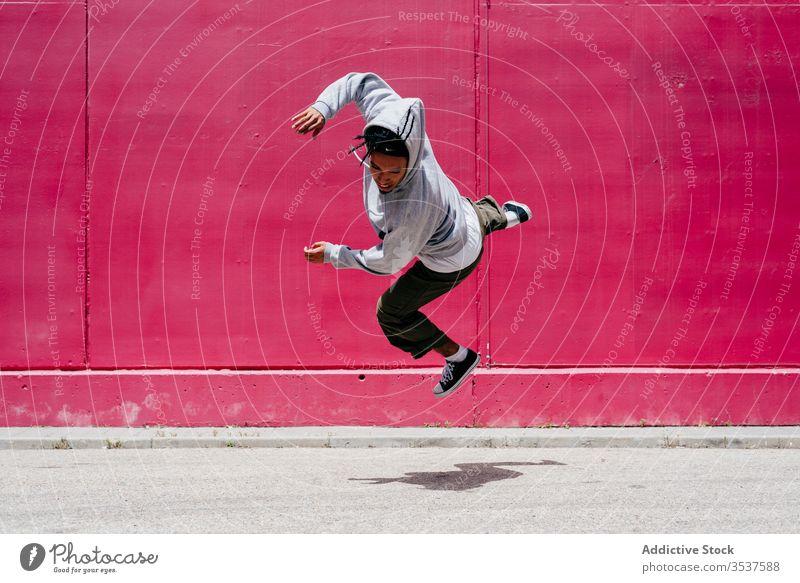 Junge hispanische Männer springen in der Nähe einer rosa Mauer auf die Straße urban Tanzen Lifestyle Großstadt posierend Stehen farbenfroh Tageslicht gemischt
