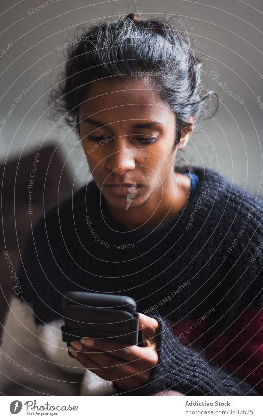 Seriöse junge ethnische Dame surft auf Smartphone Frau benutzend Komfort gemütlich Pullover Liege ruhen heimwärts Appartement Gerät Apparatur dunkles Haar