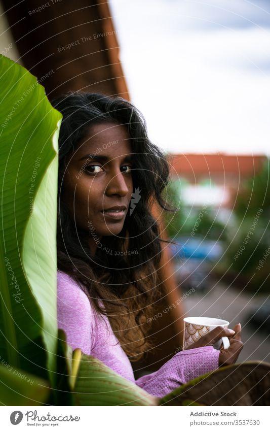 Junge Inderin mit einer Tasse Heißgetränk auf der Terrasse Frau nachdenklich Balkon Kaffee Morgen ruhen warm emotionslos Getränk Lächeln trinken schön