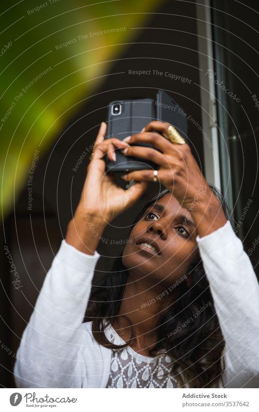 Konzentrierte indische Frau fotografiert auf Smartphone fotografieren Pflanze Balkon Konzentration Fotokamera Mobile Telefon benutzend ethnisch Inder
