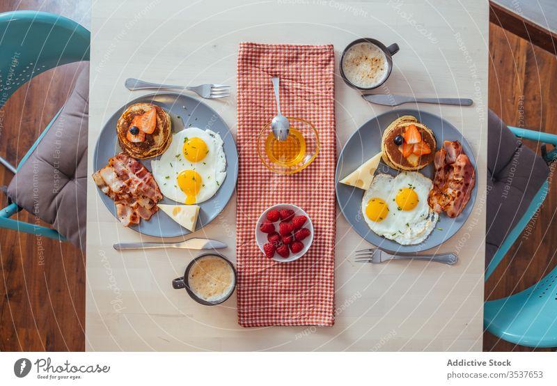 Leckere Spiegeleier mit Speck und Käse zum Frühstück Teller Ei Muffins erdbeeren schwarze Beeren Liebling Lebensmittel dienen Mahlzeit gebraten Pfannkuchen