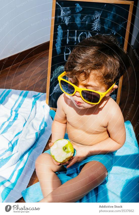 Glücklicher kleiner Junge mit Sonnenbrille, der zu Hause am Strand sitzt und vom Sommer träumt heimwärts Selbstisolierung Spaß träumen soziale Distanzierung