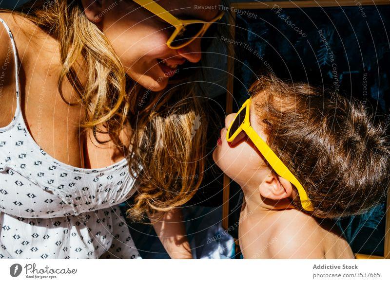 Positive Mutter spielt mit Sohn mit gelber Sonnenbrille an sonnigem Tag heimwärts Strand Liebe träumen Zusammensein Quarantäne Selbstisolierung