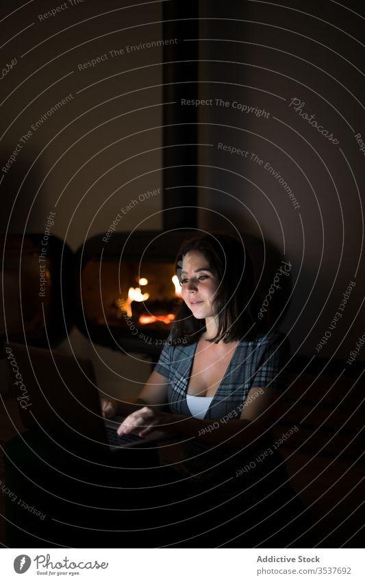 Nachdenkliche Frau surft abends zu Hause am Laptop Abend Feuerstelle gemütlich lesen ruhen benutzend besinnlich nachdenken nachdenklich heimwärts Raum dunkel