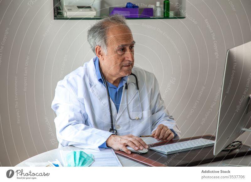 Älterer männlicher Arzt führt telemedizinische Beratung per Laptop in der Klinik durch arzt Telemedizin konsultieren Mann älter Gesundheitstelematik Ausbruch