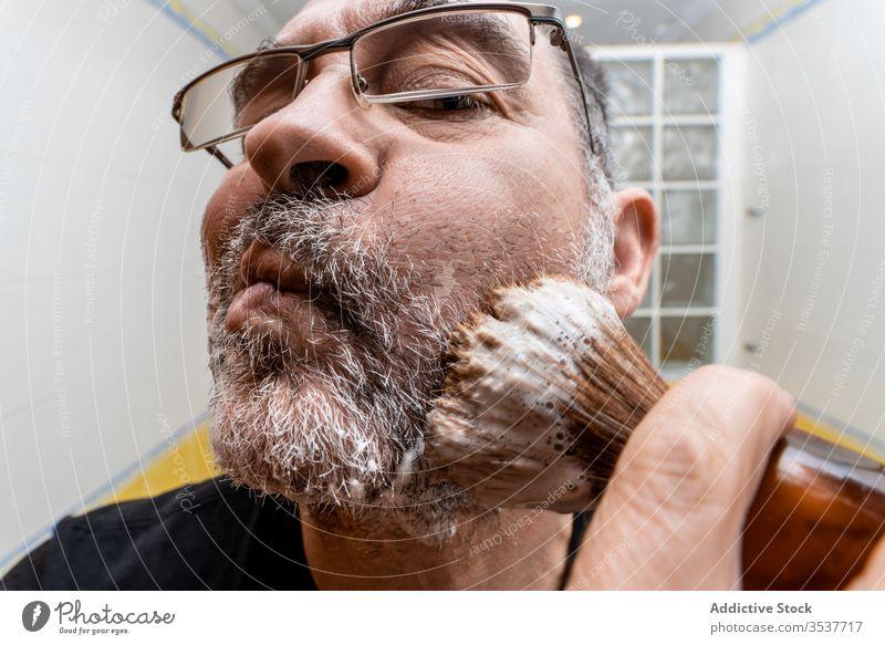 Mann trägt Rasierschaum mit Pinsel auf Rasieren schäumen Bürste bewerben vorbereiten Vollbart reif Bad Verfahren Hygiene Pflege männlich Lebensmitte Routine