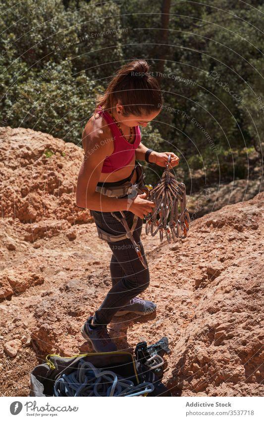 Sportliche Bergsteigerin bereitet Ausrüstung für den Aufstieg vor Frau Alpinist Gerät Klippe Felsen extrem Natur Aufsteiger Abenteuer Training Athlet