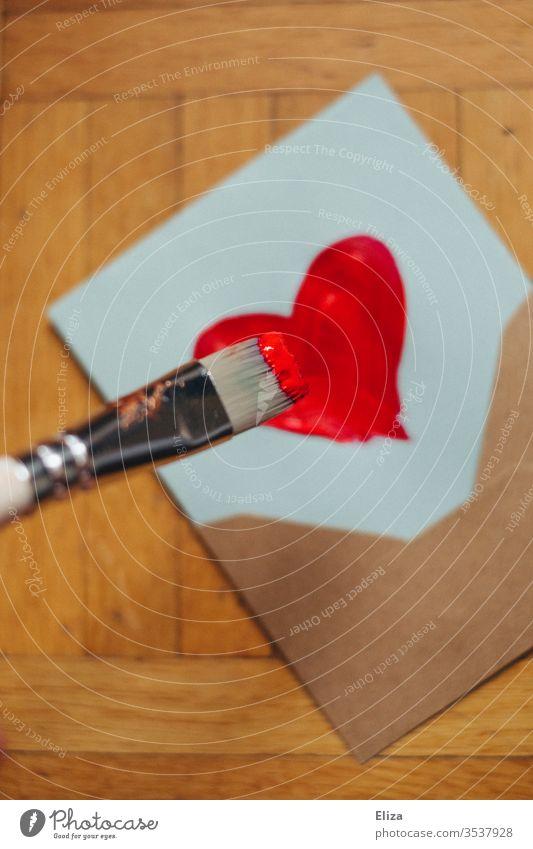 Ein Pinsel der mit roter Farbe ein Herz auf einen Brief malt Briefumschlag Liebesbrief malen Muttertag künstlerisch Malerei Emotionen Gefühle Post Valentinstag