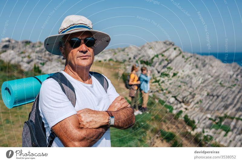 Älterer Mann beim Trekking mit Blick in die Kamera Senior reif in die Kamera schauen Landschaft Wanderung Natur Wanderer Sommer Berge u. Gebirge Erholung Hut