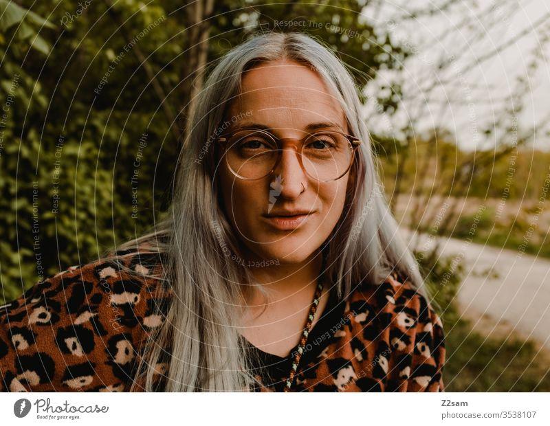 Ich freu mich, wenn sie ... Mädchen leopardenmuster Pullover sitzen Bank Natur Punktschrift Dschungel lächeln zufrieden glücklich trendy blond lange haare urban