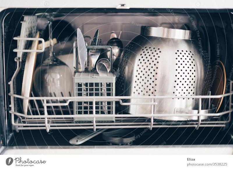 Sauberes Geschirr in einer kleinen Spülmaschine sauber Haushalt Geschirrspüler Geschirrspülen Besteck silber Haushaltsführung Küche Nudelsieb eingeräumt offen