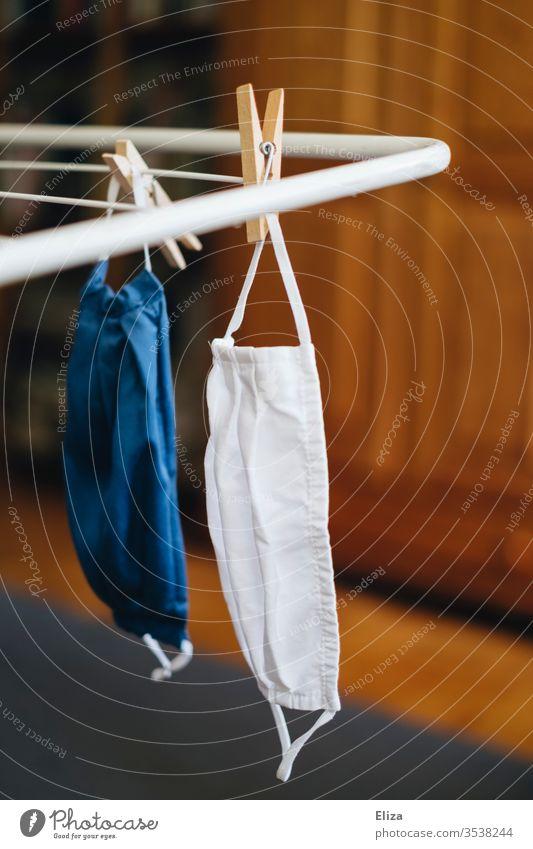 Zwei Gesichtsmasken hängen nach dem Waschen zum trocknen am Wäscheständer Stoffmaske waschen 60 grad Maske mundschutz stoff Community-Maske Blau Waschmaschine