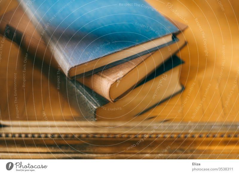 Ein Stapel mit 3 alten Büchern und einem Goldrand am unteren Bildrand lesen gold vintage Antiquariat antiquarisch Literatur Bildung Bibliothek Wissen Haufen