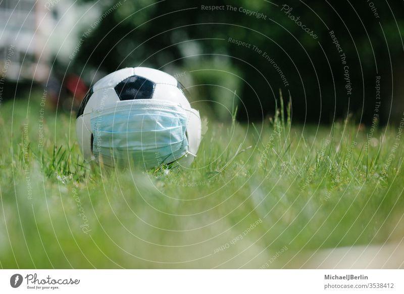 Fussball mit Gesichtsmaske für den Sport während der Covid-19-Pandemie Fußball Konzept Korona covid-19 COVID19 Gefahr Seuche Feld Spiel Gras Gesundheit Hygiene