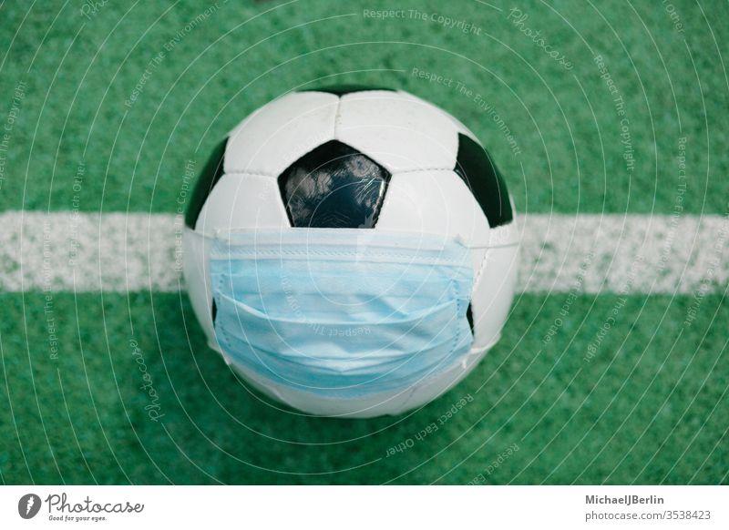 Fussball mit Gesichtsmaske für den Sport während der Covid-19-Pandemie Fußball künstlich Konzept Korona covid-19 COVID19 Gefahr Seuche Feld Spiel Gras grün