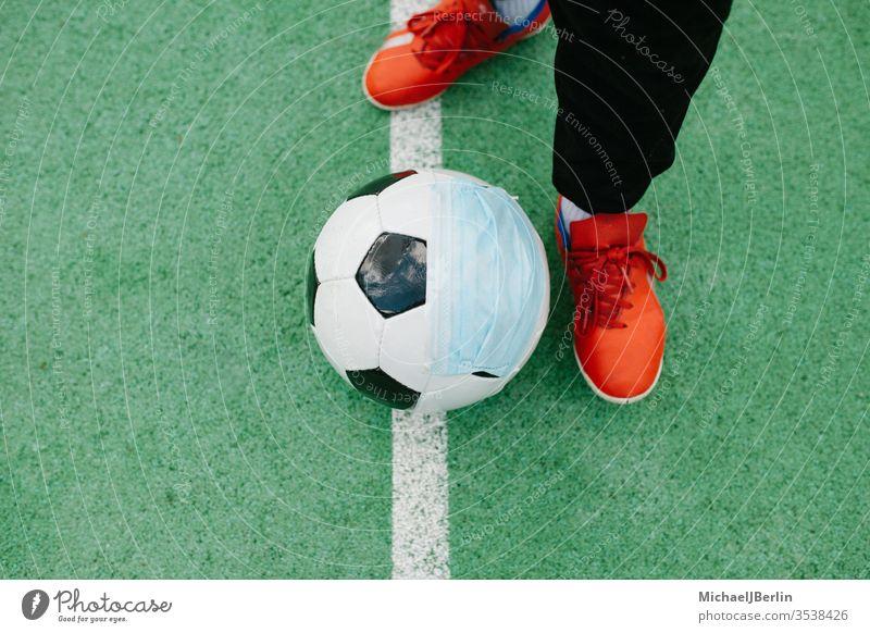 Anpfiff mit Fussball mit Gesichtsmaske für den Sport während der Covid-19-Pandemie Fuß Fußball künstlich Konzept Korona covid-19 COVID19 Gefahr Seuche Feld