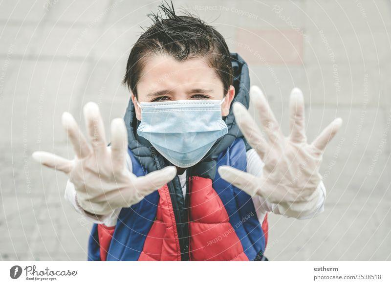Nahaufnahme eines Kindes, das eine medizinische Maske trägt und die Hände nach oben streckt Coronavirus Virus Seuche Pandemie Quarantäne covid-19 Symptom