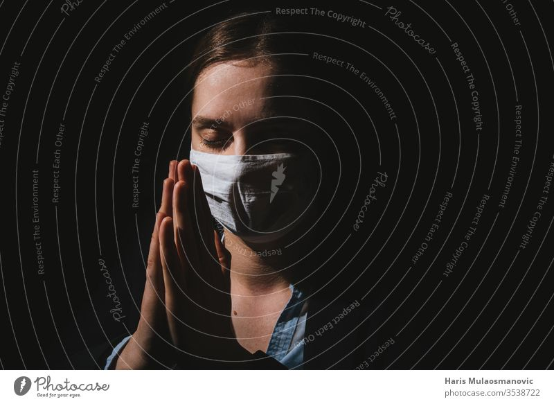Religiöse Frau mit Maske, die mit Händen dafür betet, dass Coronavirus covid-19 auf schwarzem Hintergrund endet Erwachsener schwarzer Hintergrund Kaukasier