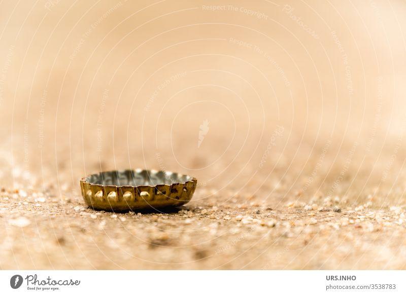 Ein Kronkorken auf sandigem Boden bleibt selten alleine kronkorken bierverschluss boden weggeworfen liegen gold beige flaschenverschluss close up nahaufnahme